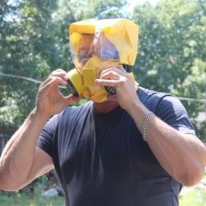 Инструктор демонстрирует, как надевать самоспасатель.